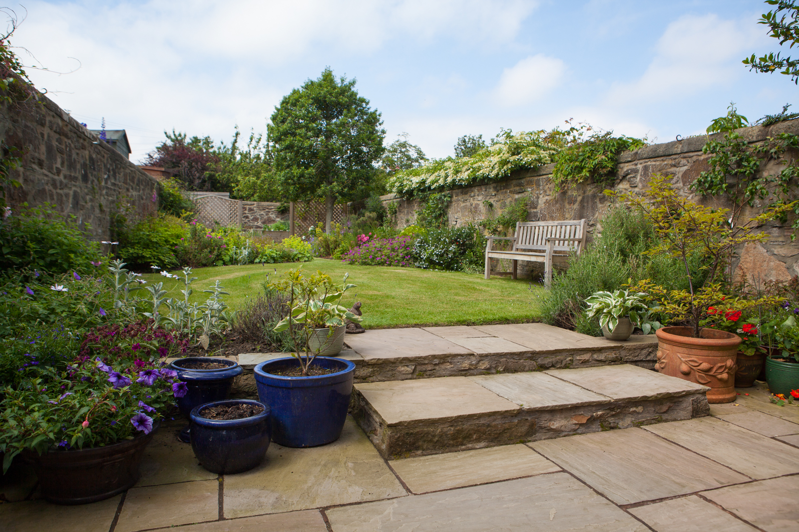 A multi level walled garden with various seating areas